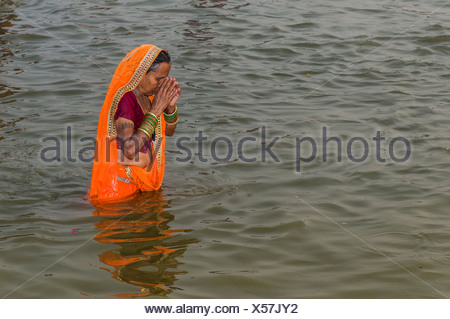 Woman wearing an orange sari taking a bath in the Sangam, the confluence of the rivers Ganges, Yamuna and Saraswati, in the - Stock Photo