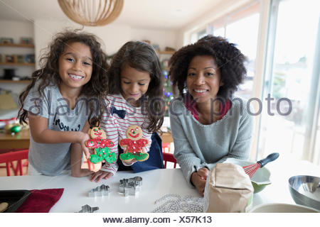 Portrait smiling mother and daughters decorating Christmas gingerbread cookies in kitchen - Stock Photo