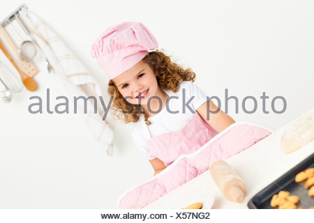 Portrait of a cute girl preparing cookies - Stock Photo