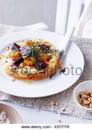 Beetroot, goats cheese and hazelnut pizza on white plate - Stock Photo