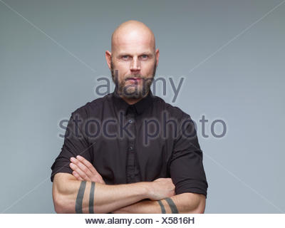 Portrait of man with bald and full beard in black in front of grey background - Stock Photo