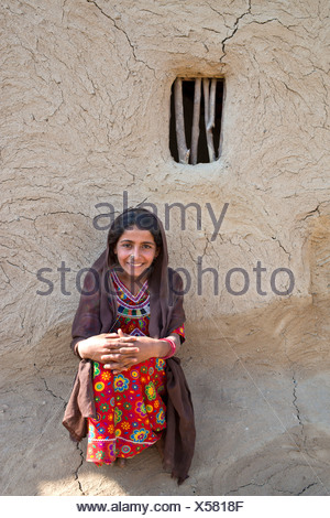 Smiling girl wearing a headscarf and traditional clothing sitting in front of a house wall with a window opening, Rann of Kutch - Stock Photo