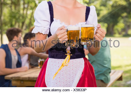 Pretty oktoberfest girl holding beer tankards - Stock Photo
