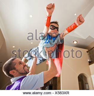 Father holding aloft his son (8-9) dressed up in fancy dress costume - Stock Photo