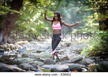 Young female hiker stepping over forest river rocks - Stock Photo