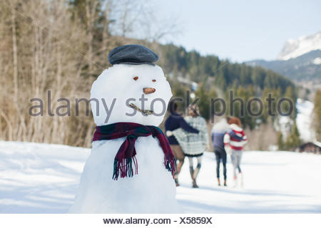Snowman, people walking in background - Stock Photo