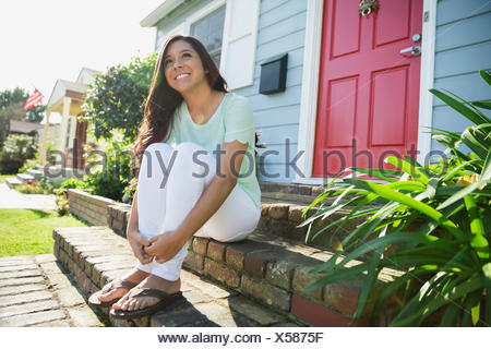Smiling brunette teenage girl sitting sunny front stoop - Stock Photo