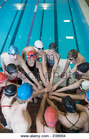 Swimming team connecting hands in huddle at swimming pool - Stock Photo