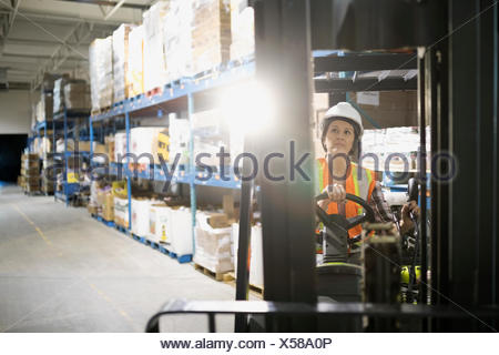 Female worker driving forklift in distribution warehouse - Stock Photo
