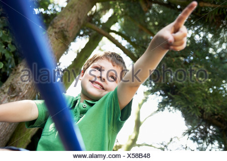 Young Boy sitting on monkey bars pointing, close up - Stock Photo