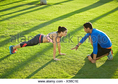 Personal trainer with woman doing plank exercise - Stock Photo