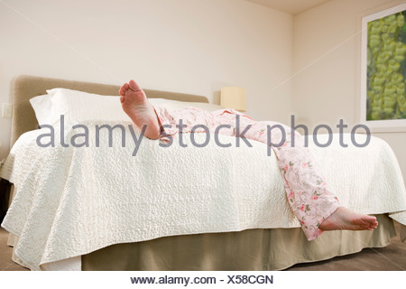 Legs of woman sprawled on bed in pajamas - Stock Photo