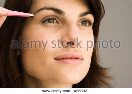 Young woman tweezing eyebrows - Stock Photo