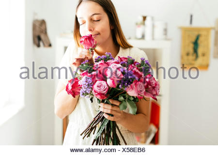 Woman smelling bouquet of roses - Stock Photo