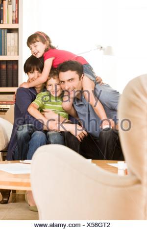 family sitting on sofa - Stock Photo