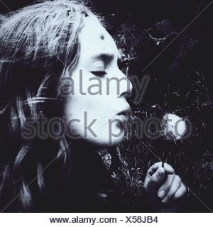 Close-Up Of Woman Blowing Dandelion - Stock Photo