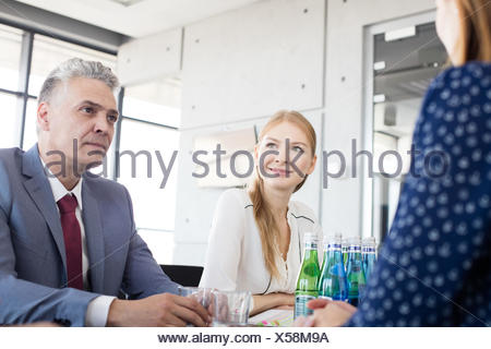 Smiling young businesswoman with colleagues in board room - Stock Photo