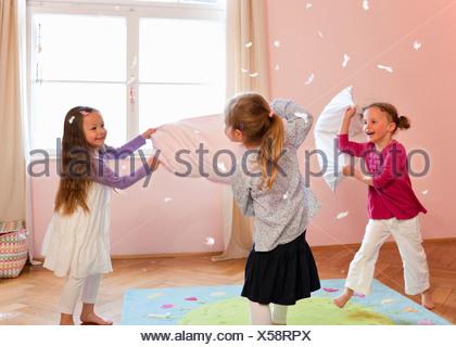 Girls having a pillow fight - Stock Photo