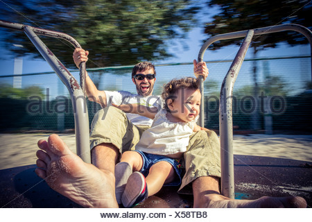 Father and toddler daughter spinning on park roundabout - Stock Photo