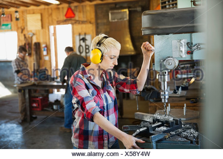 Female welder using drill press with colleagues working in background - Stock Photo