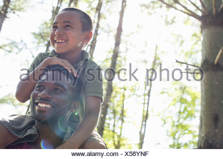 A boy sitting on his father's shoulders - Stock Photo