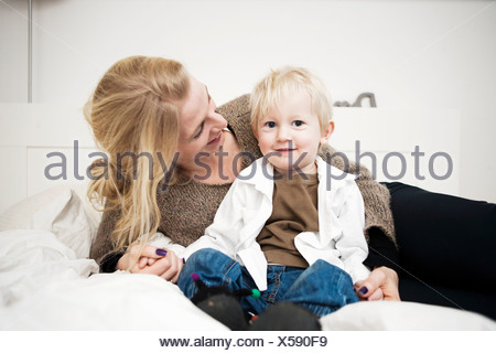 Portrait of mother holding hands with toddler son on bed - Stock Photo