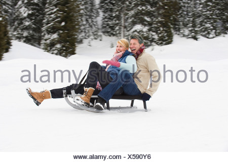 Italy, South Tyrol, Seiseralm, Couple sledding downhill, laughing, portrait - Stock Photo