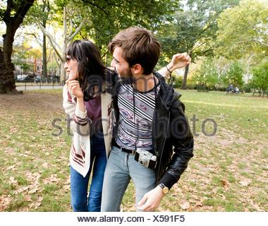 Happy young hipster couple fooling around in park - Stock Photo