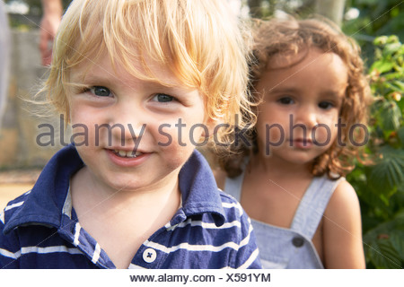 Two young boys playing in garden - Stock Photo