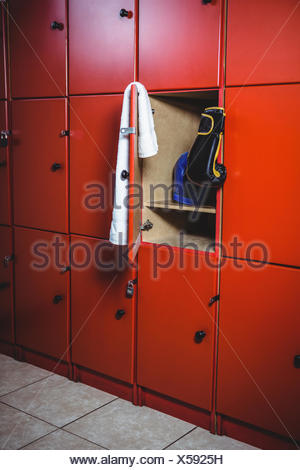 Boxing gloves and a towel in locker room - Stock Photo