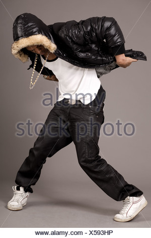 Man performs hip pop steps on grey background - Stock Photo