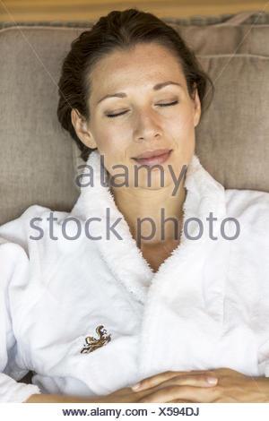 Dunkelhaarige Frau im Bademantel, entspannt in Ruheraum (model-released) - Stock Photo