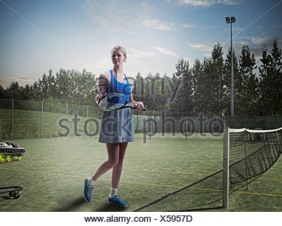 Woman standing on tennis court - Stock Photo