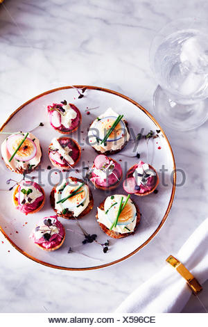 Quails egg and goats cheese canapés on plate, overhead view - Stock Photo