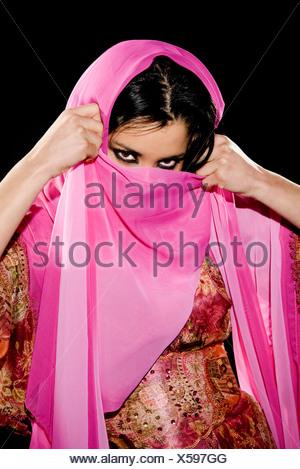 Arabian woman wearing traditional dress on black background - Stock Photo