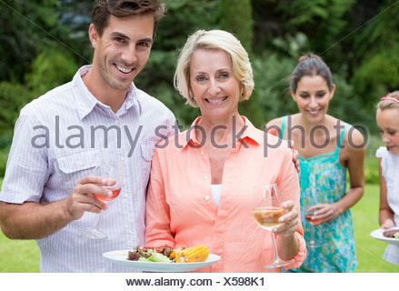 Portrait of smiling mother and son with barbecue and wine - Stock Photo