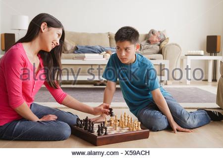 USA, California, Los Angeles, Siblings playing chess game - Stock Photo