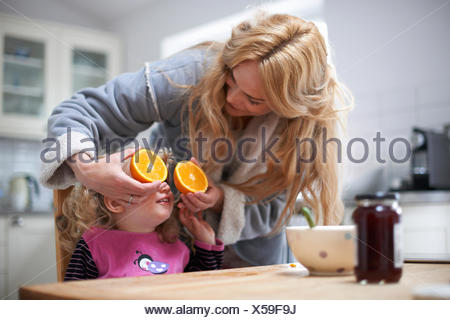 Young girl sitting at kitchen table, mother holding halved orange in front of daughter's eyes - Stock Photo