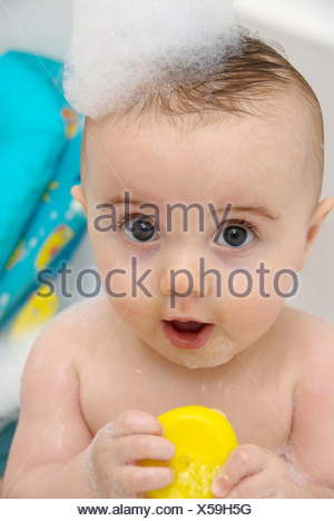 A female baby fair hair, sitting in bath bath bubbles on her head, holding a yellow duck, mouth open, looking at camera Joel - Stock Photo