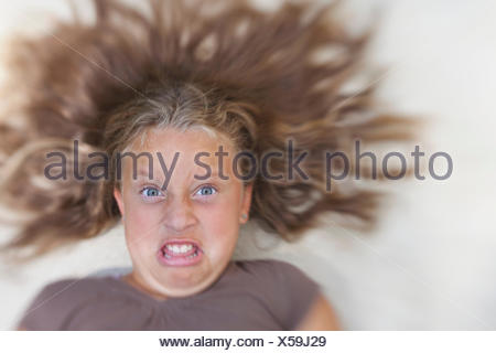 USA, Maryland, Howard County, Dayton, Girl (8-9) with tousled blond hair making a face - Stock Photo