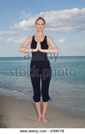 Mid adult woman in yoga pose on beach - Stock Photo