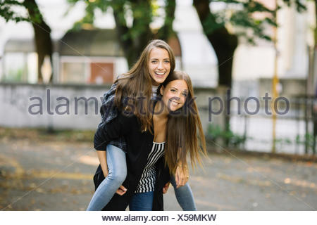 Portrait of young woman giving best friend a piggy back in park - Stock Photo