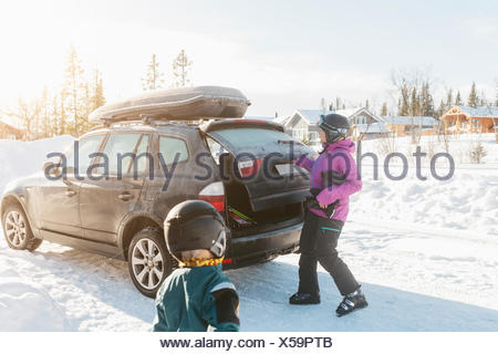 Mother and son by a car during winter - Stock Photo