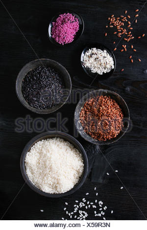 Variety assortment of raw uncooked colorful rice white, black, brown, pink in black bowls over burnt wooden background. Top view with space - Stock Photo