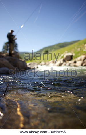 Shot of water running in the river with blurred background of a fisherman standing on the rocks. - Stock Photo