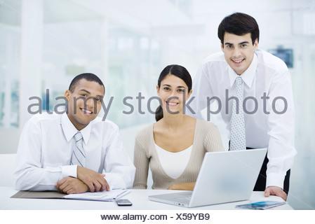 Professionals gathered around laptop computer, smiling at camera - Stock Photo