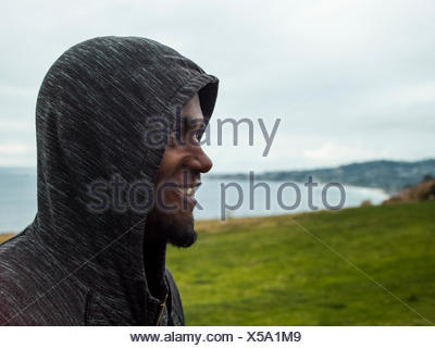 Close up of a smiling young men wearing a hoodie - Stock Photo