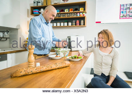 Senior couple in kitchen preparing salad - Stock Photo