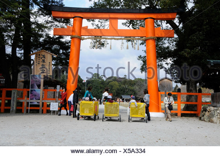 Nursery school teachers pushing mobile play pens with children of a childrens day care centre in the Kamigamo Shrine or Upper K - Stock Photo