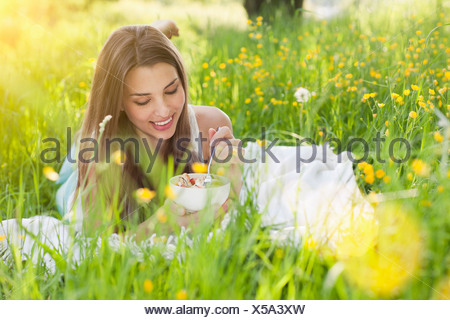 Young woman in field of buttercups eating fresh fruit - Stock Photo